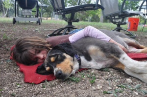 Girl lying on blanket with dog being lazy and procrastinating.