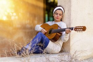 How To Find Your Strengths. Girl sitting outside playing her guitar, music is her hobby