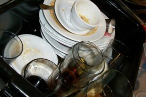 Home Cleaning Tips Tricks and Routines. Kitchen full of dirty plates and bowls after a party.