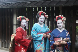 The Secret Language of Relationships. Photo of Japanese Geisha girls in full dress code and make up