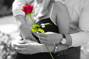 Authentic Happiness Authentic Love. A-man-hugs-a-woman from the back-and-gives-her-a-rose-red-rose-