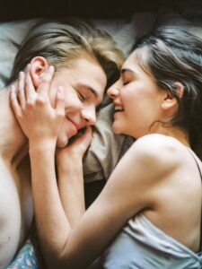 10 Secrets of a Healthy Relationship Couple in bed cuddling and talking.