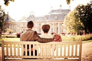 10 Secrets of a Healthy Relationship Couple sitting arms around each other quiet intimately on a bench.