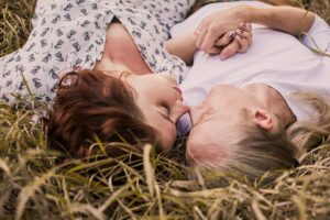 Authentic Happiness Authentic Love A man and a woman lying next to each other holding hands rubbing noses, deeply in love.
