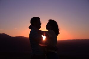 Authentic Happiness Authentic Love Girl putting her arms around a man's next and look him in the eye