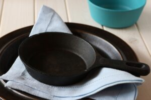 Cutlery Crockery Utensils and Food. Two cast iron pans