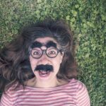 Qualities for a Good Friend. Girlfriend lying on the grass with mustache, fake glasses and thick eyebrows being funny face