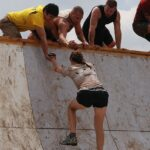 Emotional Intelligence for Good Leadership. A Team helping a girl climb an obstacle