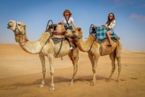 Ray-Ban Sunglasses. Two-ladies-with-sunglasses-in-the-desert-on-camels-