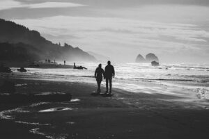 Agree to Disagree and not Argue. Couple walking hand in hand on a beach sorting out a problem