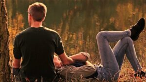 A couple-sitting-in-nature-and-chat-intimately-
