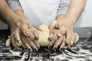 Man-embrasing-woman-from-her-back-and-knead-dough-together putting his hands over hers.